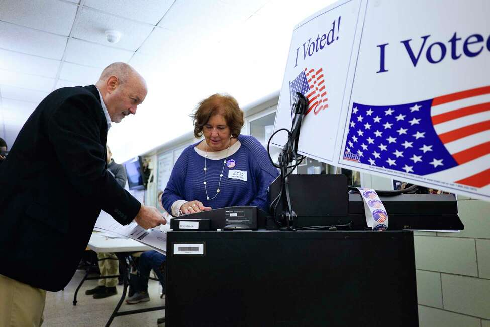 Troy Mayor Patrick Madden, left, feeds his ballot into the voting machine as election inspector Sharon Kelly looks on at School 16 on Tuesday, Nov. 5, 2019, in Troy, N.Y. (Paul Buckowski/Times Union)