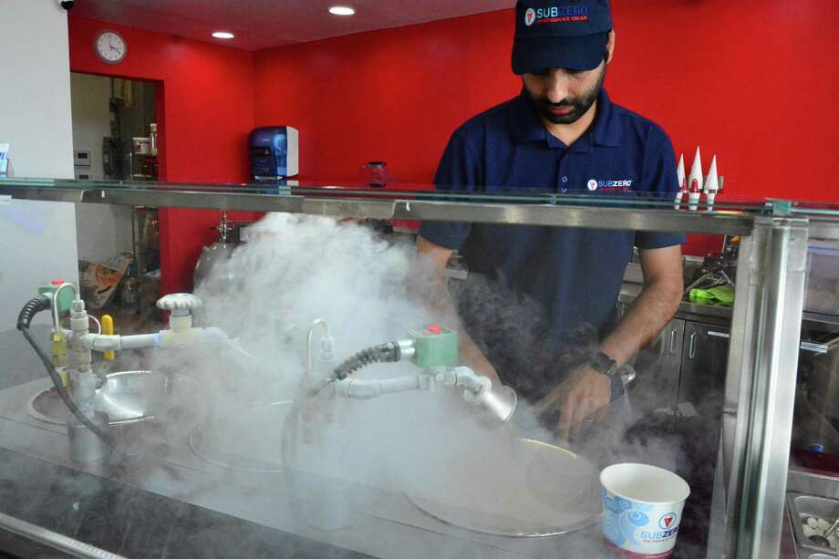 Farooq Ebrahim, co-owner of the new SubZero Ice Cream store in Pearland, is in a cloud of vapor as he prepares an order. Photo: Yvette Orozco / Yvette Orozco
