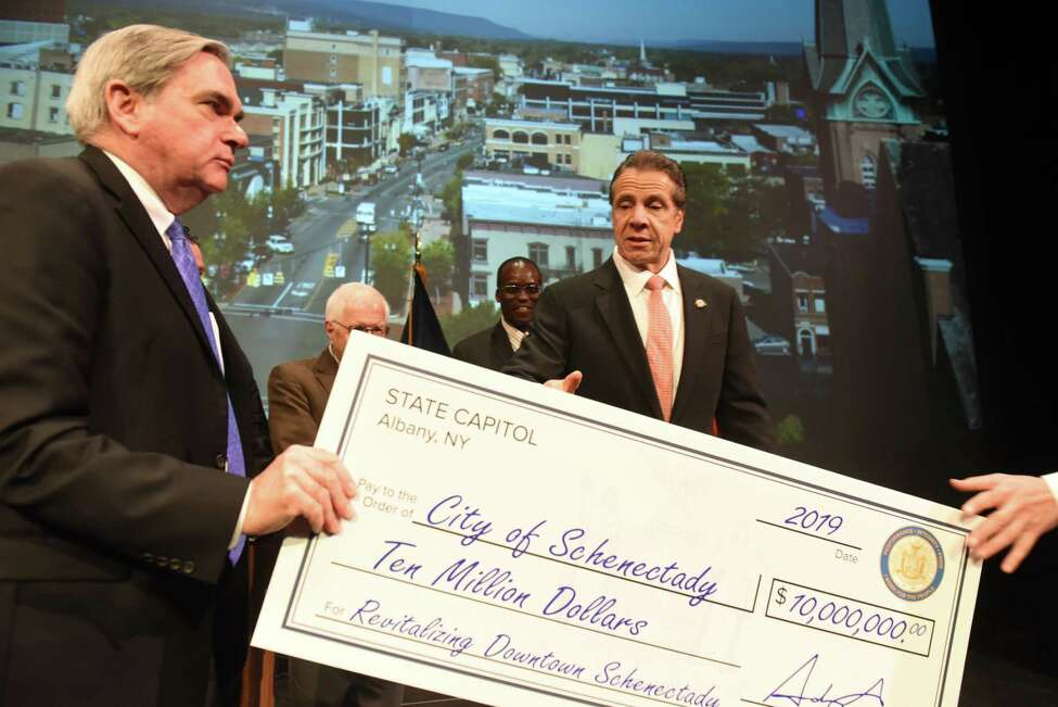 Mayor Gary McCarthy, left, and Gov. Andrew Cuomo, right, prepare to be photographed with a symbolic $10 million check for the revitalization of Downtown Schenectady on Tuesday, Nov. 5, 2019, during an announcement at Proctors Theatre in Schenectady, N.Y. The money was awarded to the city through the fourth round of the state's Downtown Revitalization Initiative, which invests annually in 10 plans across the state that are intended to turn around local communities. (Will Waldron/Times Union)