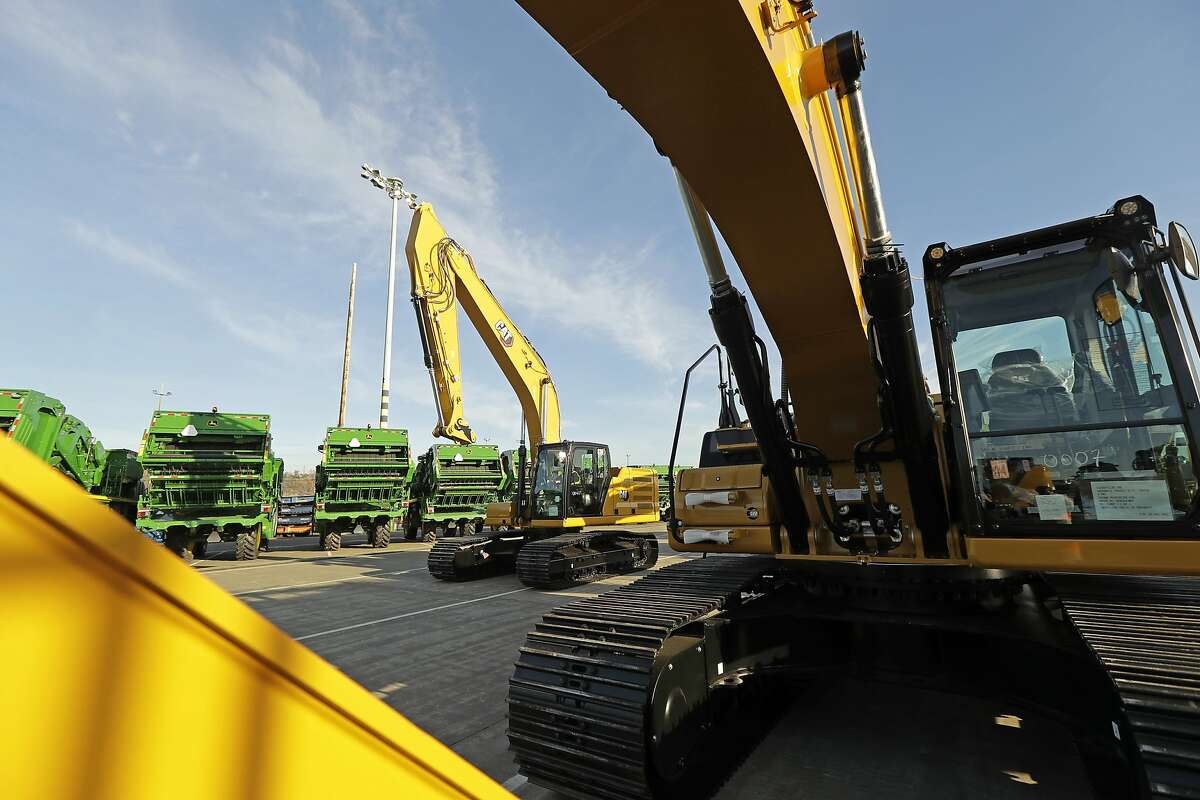 In this Monday, Nov. 4, 2019, photo John Deere Farm and Cat construction equipment made by Deere & Company and Caterpillar are shown as they are readied for export to Asia at the Port of Tacoma in Tacoma, Wash. On Tuesday, Nov. 5, the Commerce Department reports on the U.S. trade gap for September. (AP Photo/Ted S. Warren)