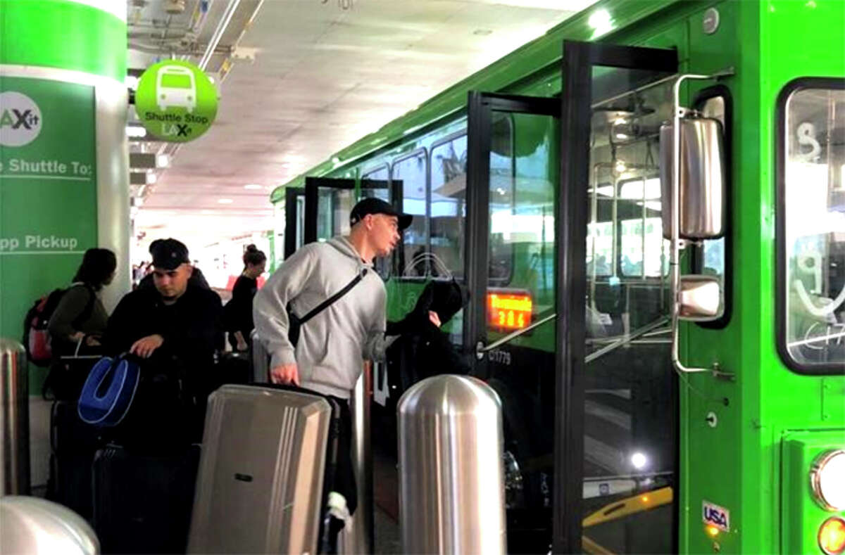 A passenger boards a bus at the terminal to LAX's new LAX-it lot for ride-sharing and taxi pick-ups.