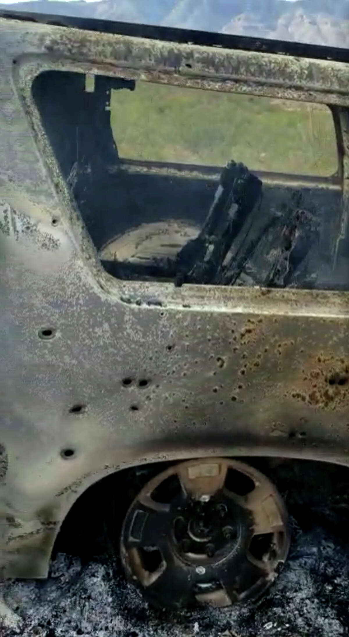 This frame from Nov. 4, 2019, video by Kenny Miller and posted on the Twitter account of Alex LeBaron shows a burned-out vehicle that was being used by some members of the LeBaron family as they were driving in a convoy near the Sonora-Chihuahua state border in Mexico. Mexican authorities say drug cartel gunmen ambushed multiple vehicles, including this one, slaughtering several women and children. (Kenny Miller/Courtesy of Alex LeBaron via AP)