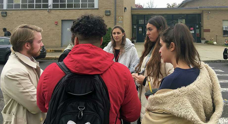 Sacred Heart students talk to Carlos Ruiz and Alessandra Leone, two of the organizers of PioneerVotes, a SHU student voting initiative. Student Maria Bonaddio said she registered to vote, but was turned away at John Winthrop Elementary in Bridgeport on Tuesday, Nov. 5, 2019. Photo: Liz Teitz /Hearst Connecticut Media