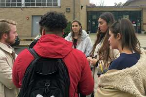 Sacred Heart students talk to Carlos Ruiz and Alessandra Leone, two of the organizers of PioneerVotes, a SHU student voting initiative. Student Maria Bonaddio said she registered to vote, but was turned away at John Winthrop Elementary in Bridgeport on Tuesday, Nov. 5, 2019.