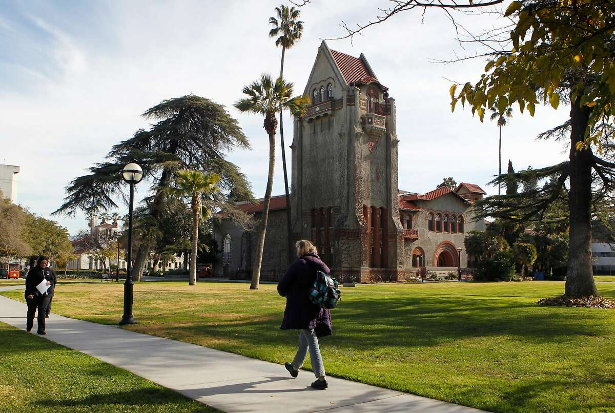 People walk past Tower Hall on the San Jose State University campus after the school announced a partnership with Udacity in San Jose, Calif. on Tuesday, Jan. 15, 2013, to offer online courses. The pilot program will begin this semester with two math classes and one statistics course.