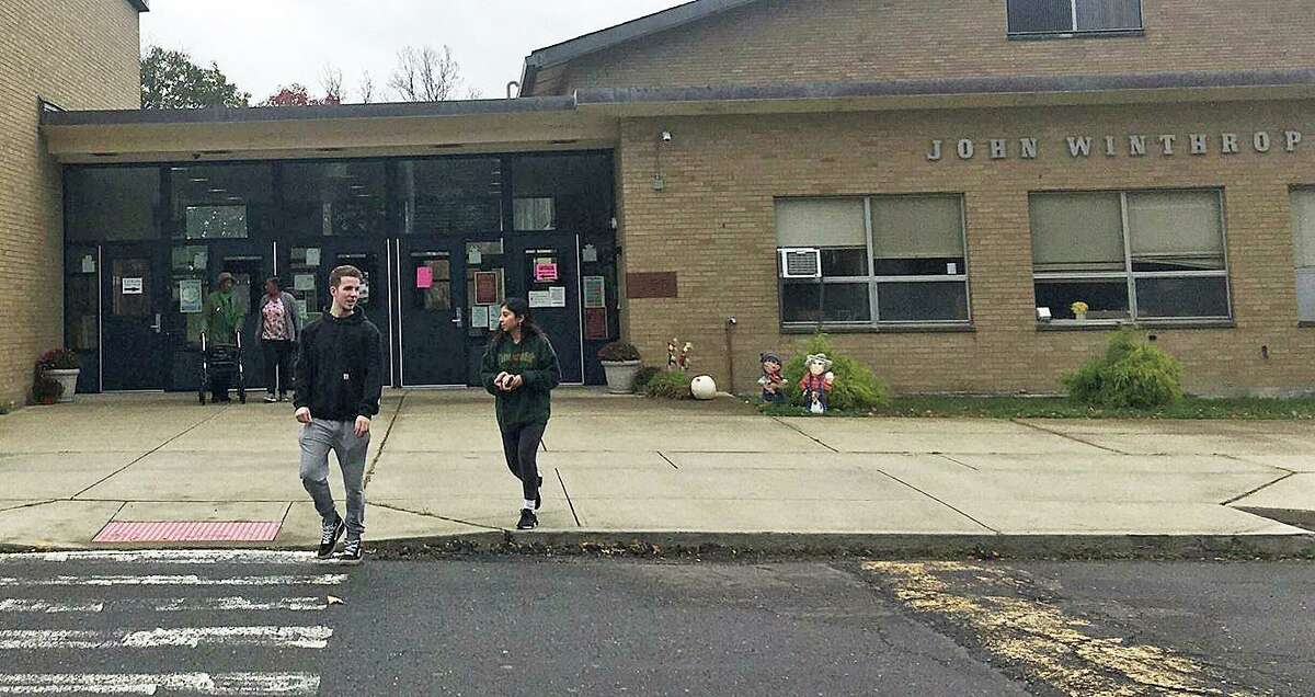 Sacred Heart students talk to Carlos Ruiz and Alessandra Leone, two of the organizers of PioneerVotes, a SHU student voting initiative. Student Maria Bonaddio said she registered to vote, but was turned away at John Winthrop Elementary.