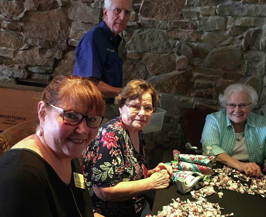 Lake Conroe Centennial Lions Club members got together recently and stuffed 500 candy rolls that will be delivered to 250 children in Mexico for Christmas.  Shown here in front, left to right, Dot Anderson, Dian Dodd, Katherine Landes. In back is Dave Underdown. Photo: Courtesy Photo