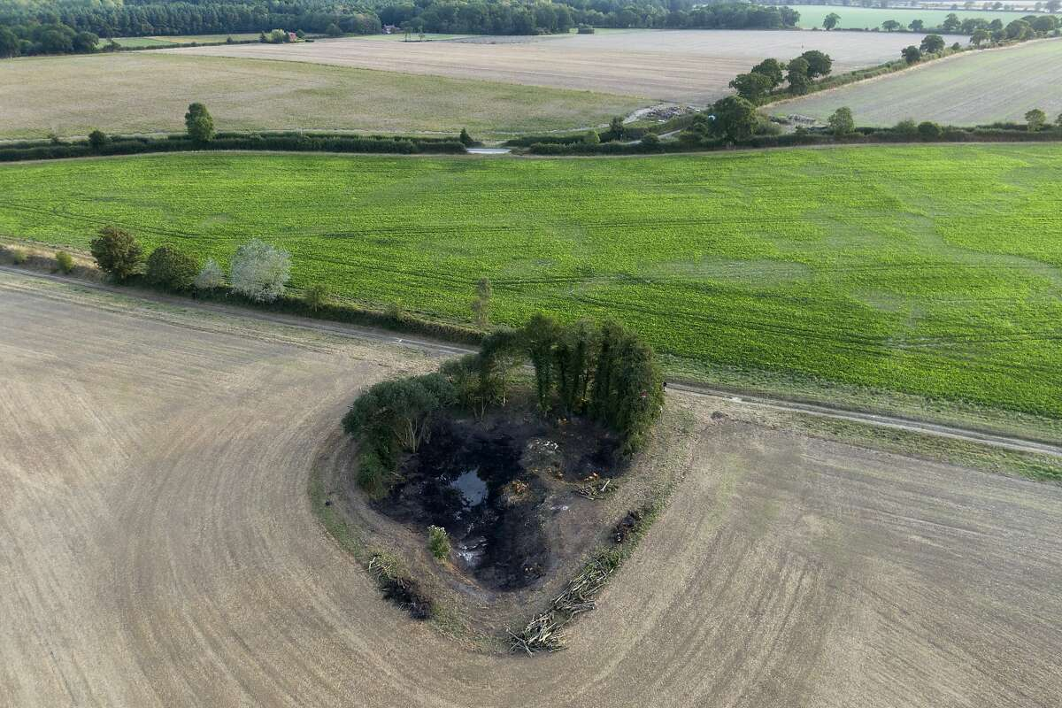 ADVANCE FOR USE TUESDAY, NOV. 5, 2019 AND THEREAFTER - A wetland is surrounded by farmland near Hindolveston, Dereham, eastern England, on Friday, Sept. 13, 2019. Around the world, efforts are being made to reclaim wetlands that have been filled in to plant crops or fill other human needs. (AP Photo/Emilio Morenatti)