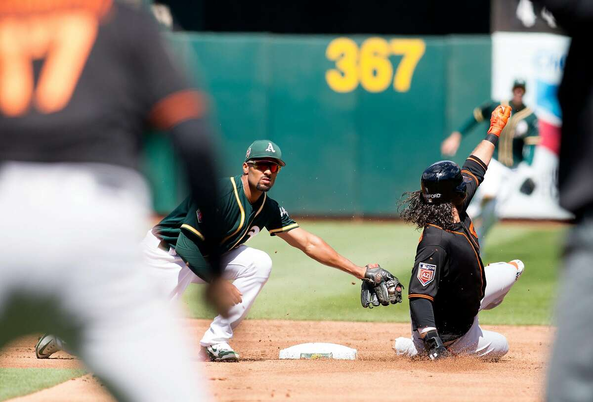 This was just practice too: Oakland Athletics shortstop Marcus Semien, left, tries to put the tag on San Francisco Giants' Brandon Crawford (35) on a hit-and-run that turned into just a foul ball during the second inning of a preseason Major League Baseball game, Sunday, March 25, 2018 in Oakland, Calif.