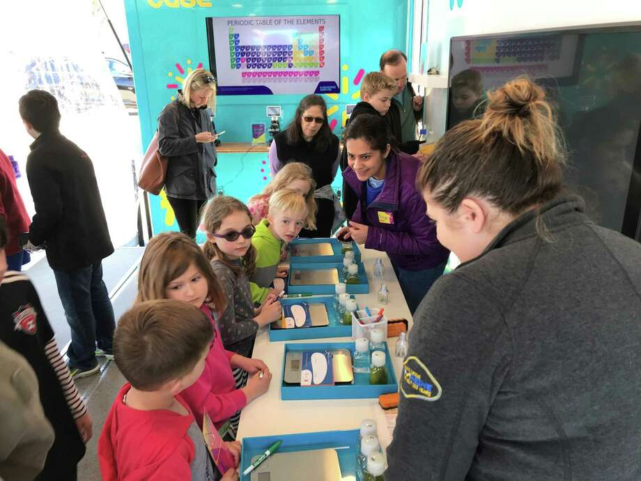 Kids test out the different experiments in the Curiosity Cube, a travelling science lab made to inspire the next generation of scientists. Photo: Provided