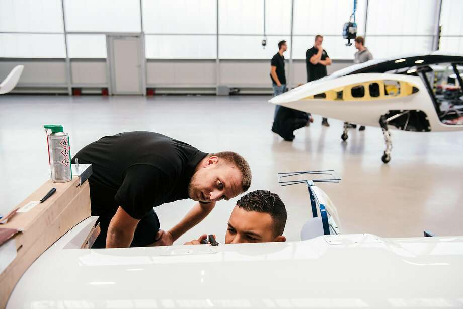 Above: Lilium employees work on a disassembled wing of the company's prototype flying taxi in Wessling, Germany. Below: The taxi, which will face competition from about 20 other companies, sits in a hangar. Photo: Photos By Felix Schmitt / New York Times