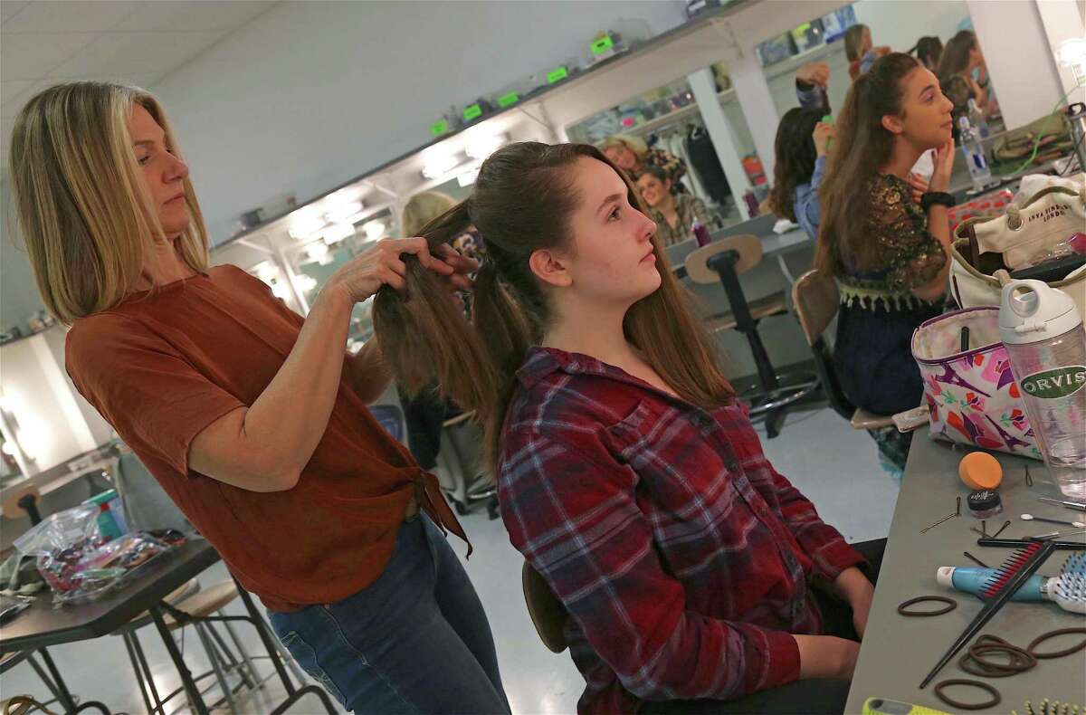 Remy Young, 16, at right, finishes her makeup , while parent volunteer Sally Eiler helps Erin Dillon, 17, with her hair for the performance of