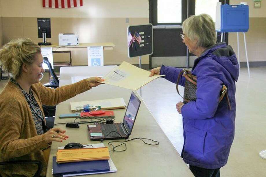 Election Inspector Erin Weber hands a ballot to a Bad Axe resident so she can vote Nov. 5. Elections were held in the cities of Bad Axe and Caseville, as seats on each city council were up for grabs. (Scott Nunn/Huron Daily Tribune)