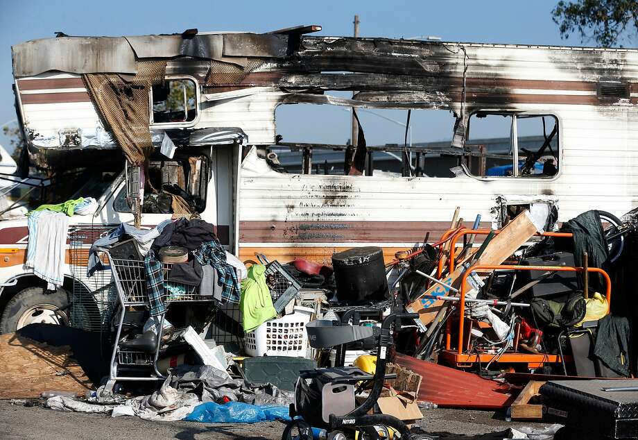 A recreational vehicle destroyed by fire and debris remains at a homeless encampment in Oakland. Photo: Paul Chinn / The Chronicle