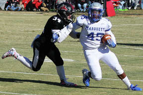 Marquette Catholic running back Iggy McGee (45) tries to turn the corner before being taken down by Fairfield's Blake Pruitt in the first half of a Class 3A football playoff game Saturday afternoon in Fairfield.