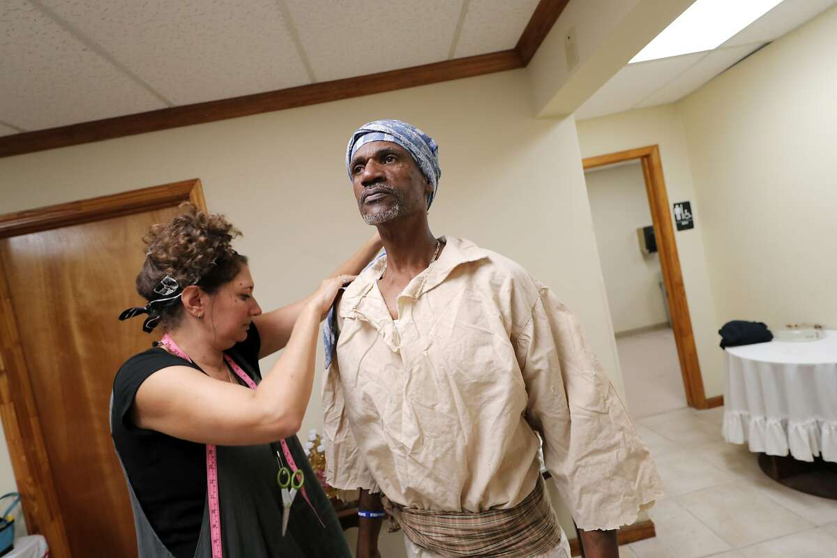 In this Oct. 23, 2019, photo, reenactor Louis Ward is fitted for his period costumes by Patricia Gorman for the upcoming reenactment of a slave rebellion in New Orleans. More than 200 years after the largest slave rebellion in American history, hundreds of reenactors will retrace their journey through the sugar plantation country of southeastern Louisiana. (AP Photo/Gerald Herbert)
