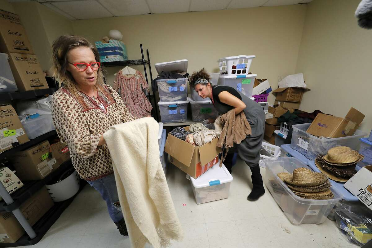 In this Oct. 23, 2019, photo, Allison L. Parker, left, and Patricia Gorman prepare period costumes for the upcoming reenactment of a slave rebellion in New Orleans. More than 200 years after the largest slave rebellion in American history, hundreds of reenactors will retrace their journey through the sugar plantation country of southeastern Louisiana. (AP Photo/Gerald Herbert)