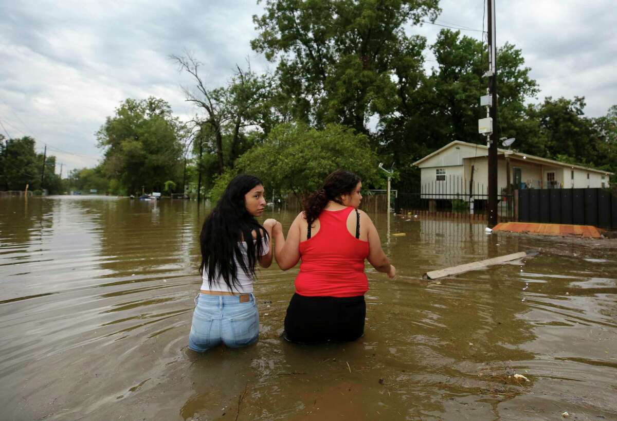 Two women make their way Sept. 19, in Houston. A reader says it may be time to abandon the vulnerable parts of Texas as climate shifts.