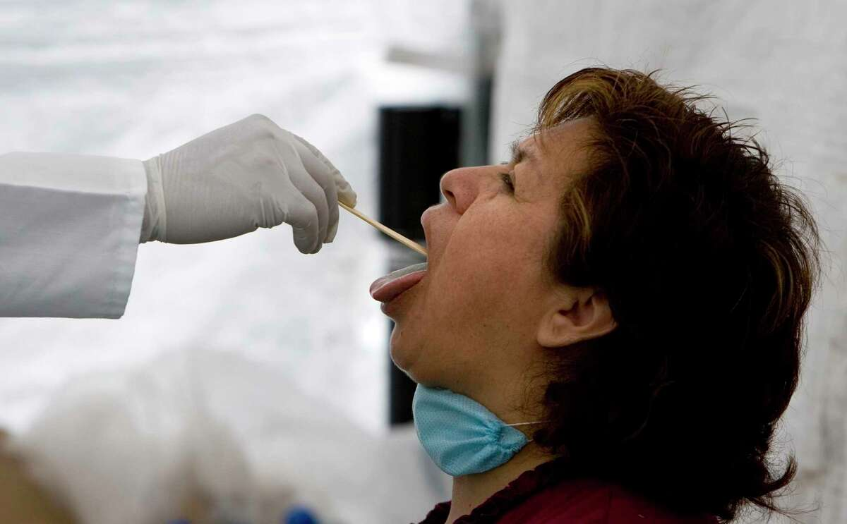 A health worker checks a woman for a possible flu infection.