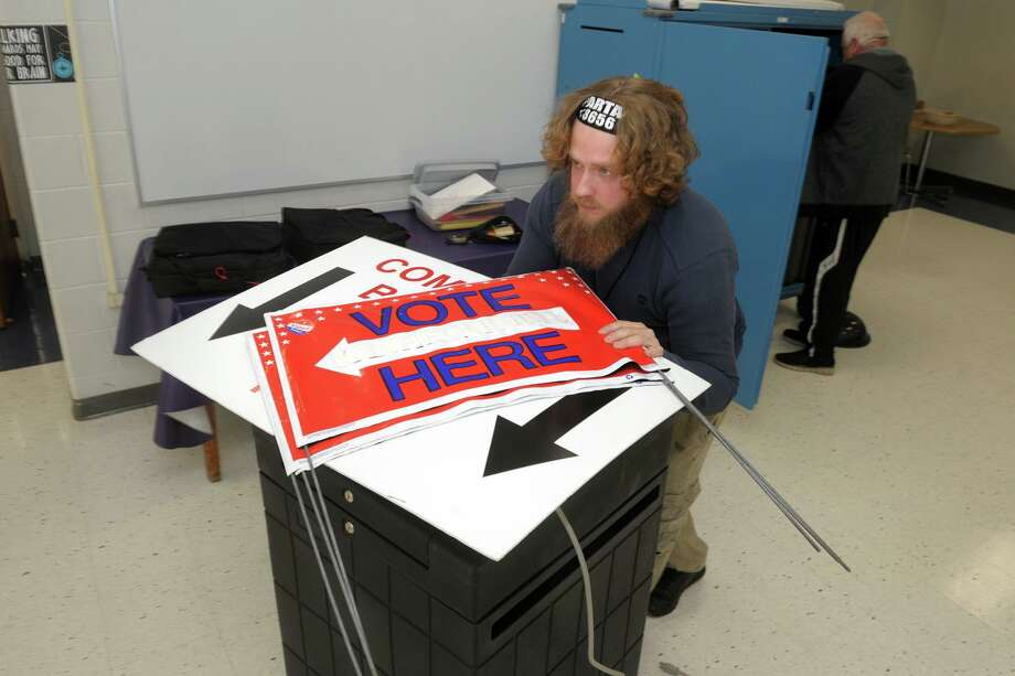 Robert Gonzalez wheels a cart of voting equipment while he and others prepare the cafeteria of Wooster Middle School for election day voting in Stratford on Monday. Photo: Ned Gerard / Hearst Connecticut Media / Connecticut Post