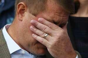 Darien's Scott Hapgood wipes away a tear beside his wife, Kallie Hapgood, during a rally in October outside Darien Town Hall.