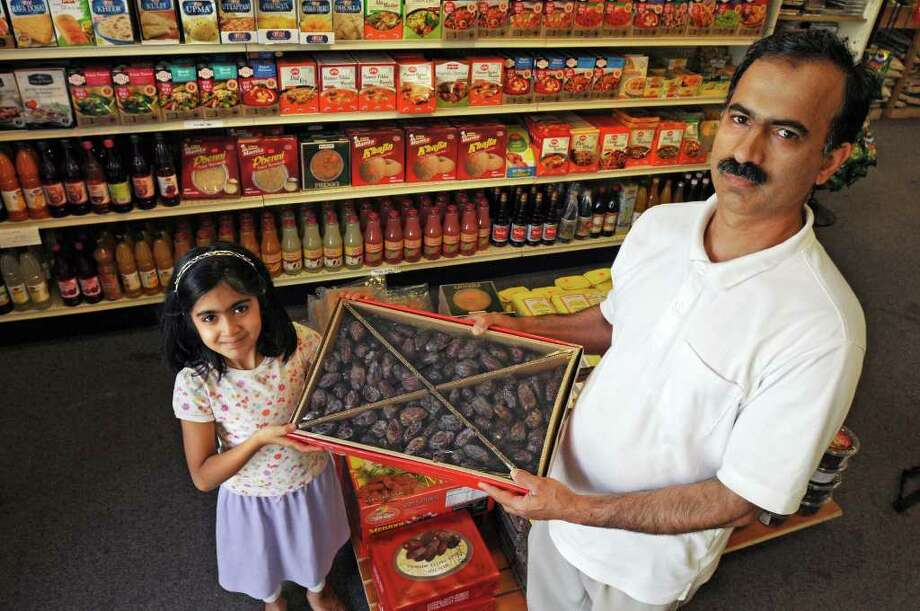 Naeem Akhtar, owner of Halal Super Market, holds a large box of sweet dates with his daughter Abeerah Akhtar in Latham.   (Lori Van Buren / Times Union) Photo: Lori Van Buren