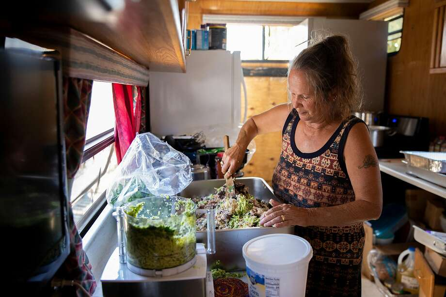 Teri Rubiolo stirs up a meal for people in need at her trailer home on Cirby Creek Road, a few miles from Paradise (Butte County). She has been cooking for victims of the 2018 Camp Fire, many of whom need to forgo food costs to pay for gas for their generators. She cooks about 100 hot meals a day. Photo: Santiago Mejia / The Chronicle