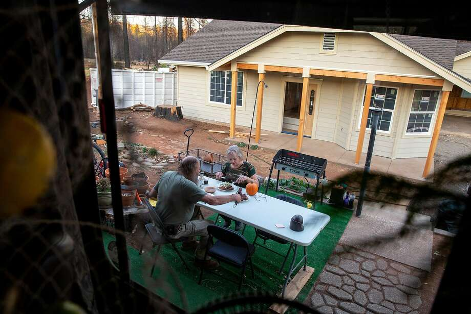 Jerry and Patty Wilson have dinner outside the trailer they are living in as they rebuild the home where they had lived 41 years. Photo: Santiago Mejia / The Chronicle