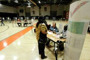 Election workers check in residents at District 12 polling site at Stamford High School on Tuesday.