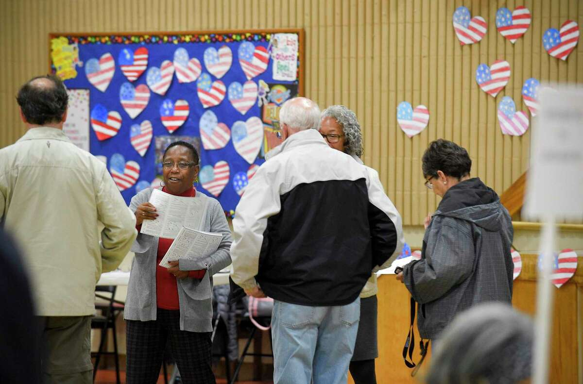 Blanche Johnson, second from left, an election worker at the District 14 polling site at Stillmeadow Elementary School, hands out ballots to residents as they cast their vote on Nov. 5, 2019 in Stamford, Connecticut.