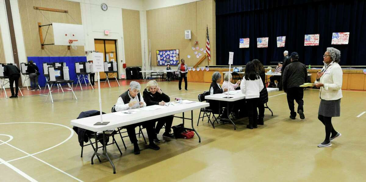 Election workers wait for resident to cast their votes at the District 14 polling site at Stillmeadow Elementary School on Nov. 5, 2019 in Stamford, Connecticut.