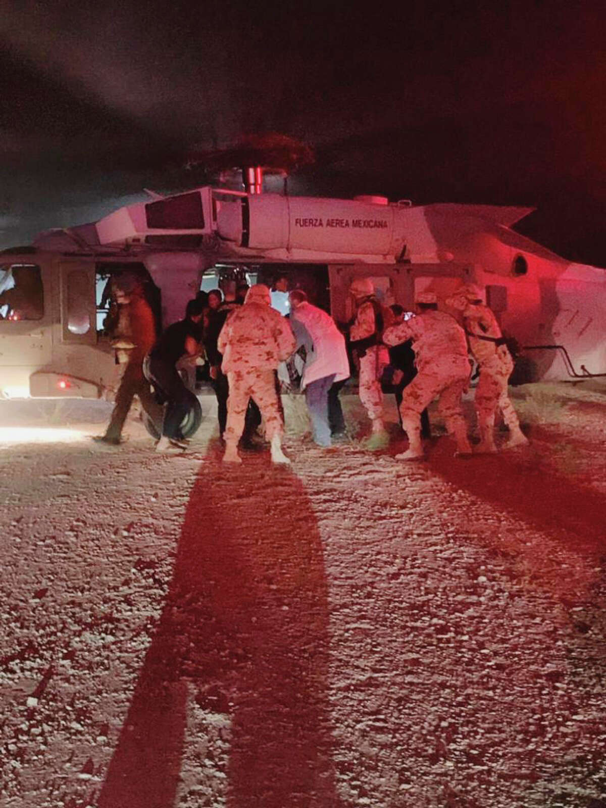 In this photo provided by the Sonora state Health Secretary, children of the extended LeBaron family, who were injured in an ambush are taken aboard a Mexican Airforce helicopter to be flown to the Mexico-U.S. border, from the border between the Mexican states of Chihuahua and Sonora, Monday, Nov.4, 2019. The children were injured when drug cartel gunmen ambushed three SUVs along a dirt road, slaughtering six children and three women, all U.S. citizens living in northern Mexico, in a grisly attack that left one vehicle a burned-out, bullet-riddled hulk. (Sonora state Health Secretary via AP)
