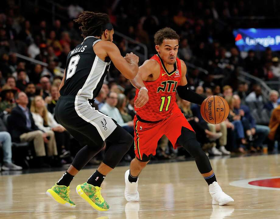 ATLANTA, GEORGIA - NOVEMBER 05:  Trae Young #11 of the Atlanta Hawks drives against Patty Mills #8 of the San Antonio Spurs in the first half at State Farm Arena on November 05, 2019 in Atlanta, Georgia.  NOTE TO USER: User expressly acknowledges and agrees that, by downloading and/or using this photograph, user is consenting to the terms and conditions of the Getty Images License Agreement. Photo: Kevin C. Cox, Getty Images / 2019 Getty Images
