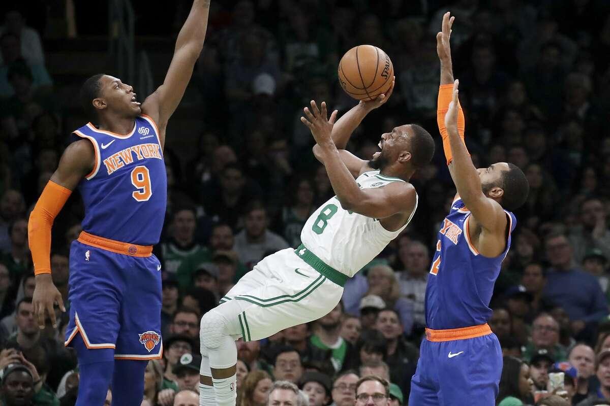 Boston Celtics guard Kemba Walker (8) shoots against New York Knicks guard RJ Barrett (9) and guard Wayne Ellington, right, in the second half of an NBA basketball game, Friday, Nov. 1, 2019, in Boston. The Celtics won 104-102. (AP Photo/Elise Amendola)
