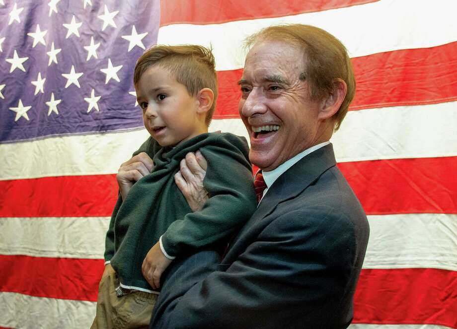 Wallingford Mayor William W. Dickinson Jr. holds his grandson William Beckett Dickinson, 5, as he stands in front of an American flag at Gaetano's Tavern on Main as he thanks family and friends after he won his 19th term as Wallingford's mayor Tuesday. Photo: Aaron Flaum / Associated Press / Record-Journal