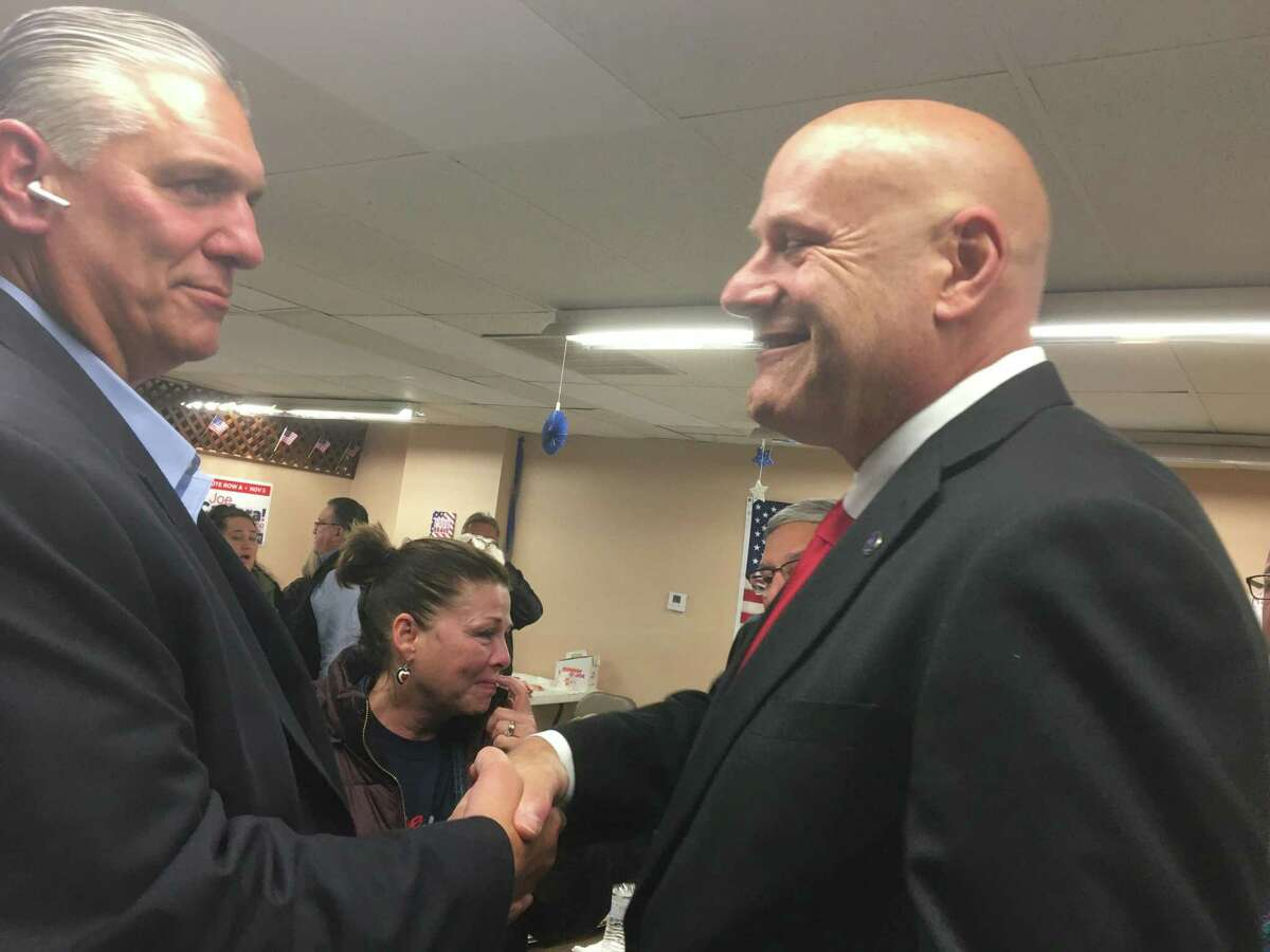 """East Haven Republican mayoral candidate """"Big Steve"""" Tracey, left, congratulates Democratic victor and Mayor-elect Joe Carfora, right, in Carfora's headquarters after Carfora defeated Tracey by a 3,865-3,169 margin on Tuesday Nov. 5, 2019. Independent petition candidate Bonifacio """"Oni"""" Sioson received 292 votes."""