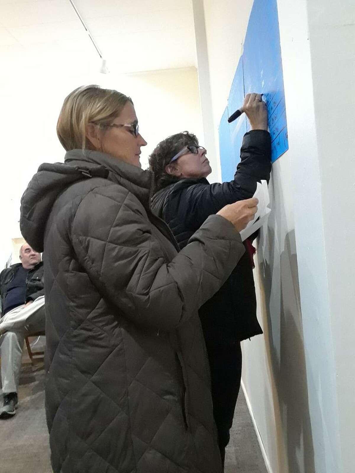 Democrat Ellen Hoehne writes voter returns as they are read to her by school board member and incumbent Democrat Fiona Cappabianca.