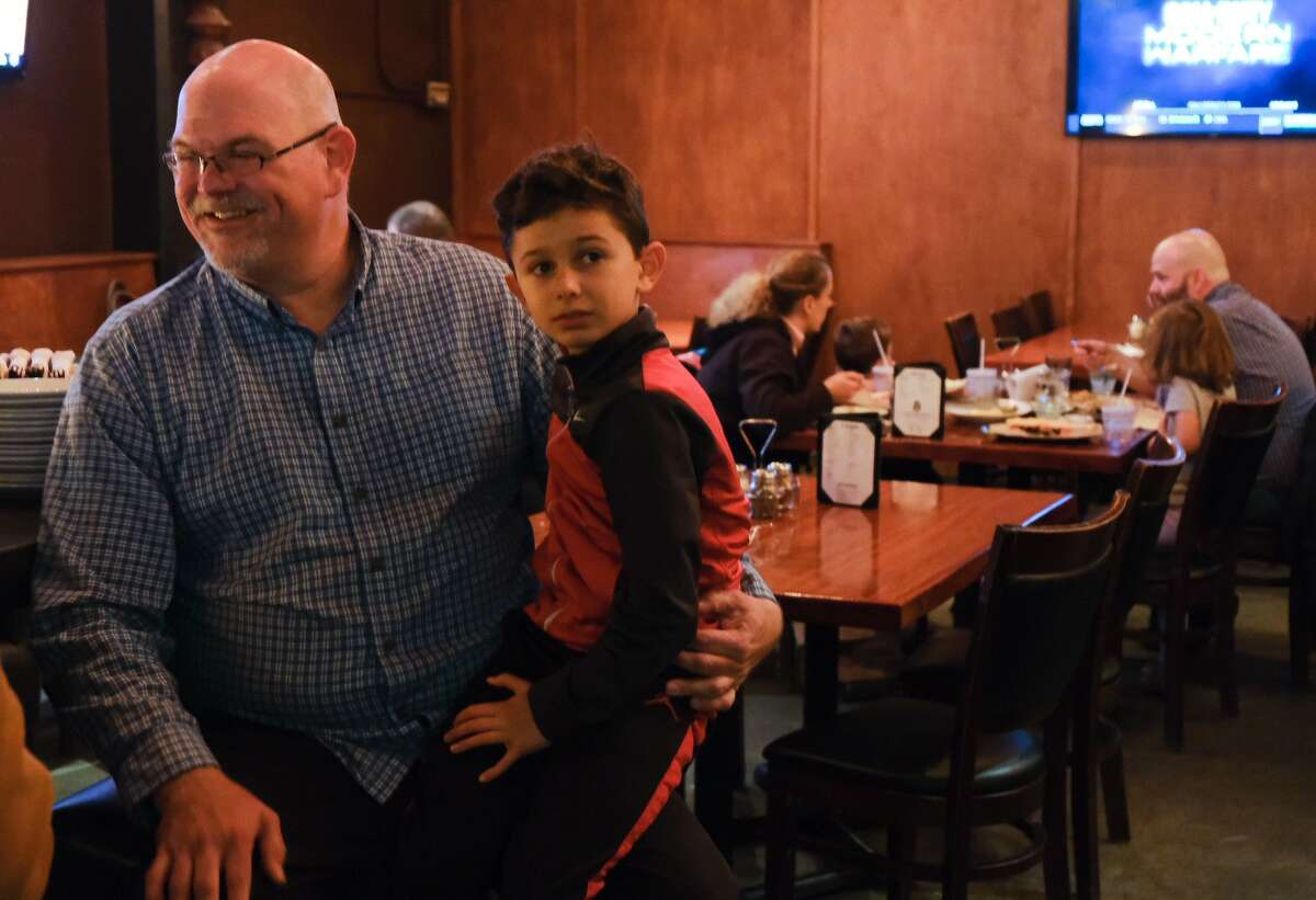Phil Tavel, candidate for Seattle City Council District 1, sits with his son.