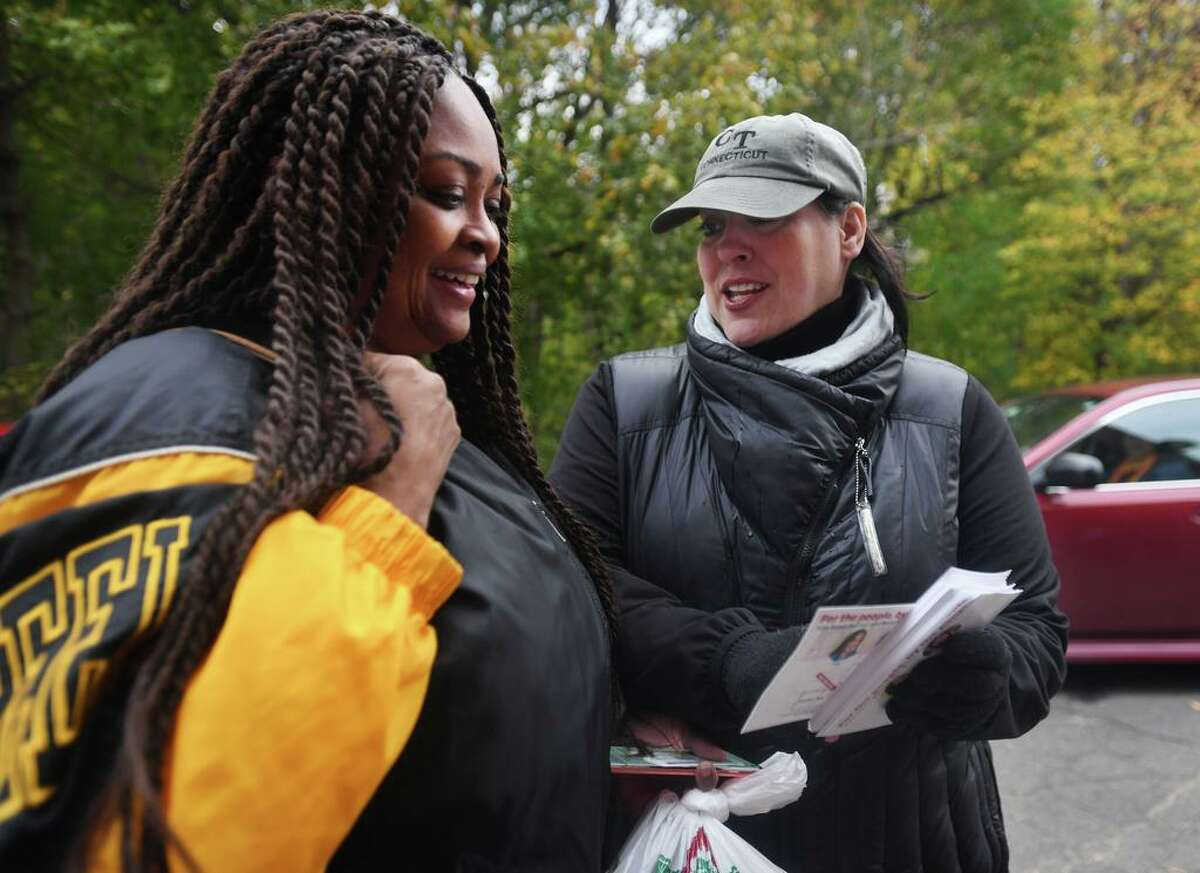 Candidate for Bridgeport Board of Education and City Council Maria Pereira, right, talks to voters outside the polls at Hooker School in Bridgeport, Conn. on Tuesday, November 5, 2019.