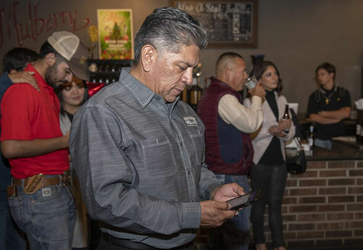 Jerry Morales checks his phone for updates 11/05/19 night as election results are late being released. Tim Fischer/Reporter-Telegram