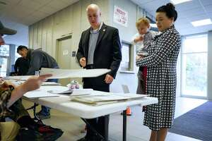 Troy mayoral candidate, Tom Reale, left, receives his ballot as he and his wife, Grace Reale voted on Tuesday, Nov. 5, 2019, in Troy, N.Y. Grace is holding their daughter, Fiammetta, 1.    (Paul Buckowski/Times Union)