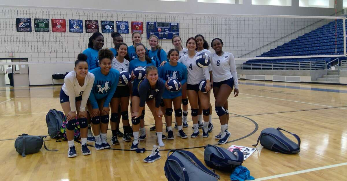 The Lamar Consolidated Mustang volleyball team poses after sweeping the Waltrip Rams in the opening round of the playoffs on Nov. 5 at Fort Bend ISD's Hopson Field House in Missouri City.