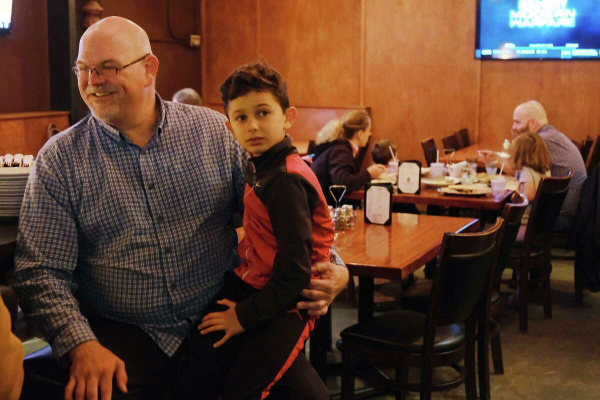 District 1 city council candidate Philip Tavel sits with his son as he and his supporters gather at Talarico's Pizza in West Seattle as they wait for the election results to come in, Tuesday, Nov. 5, 2019.
