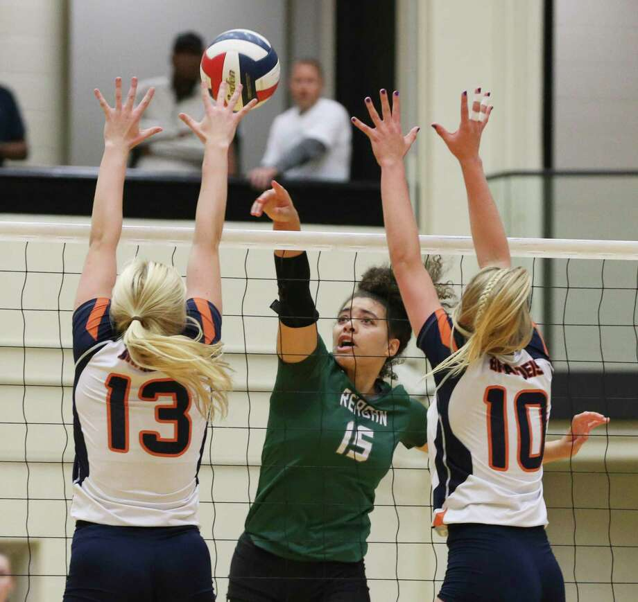 Reagan's Nyah Anderson (15) tips a shot over Brandeis' Ava Magnabosco (13) and Carlee Pharris (10) in Class 6A bidistrict high school volleyball playoff at Littleton Gym on Tuesday, Nov. 5, 2019. (Kin Man Hui/San Antonio Express-News) Photo: Kin Man Hui, Staff / Staff Photographer / ©2019 San Antonio Express-News