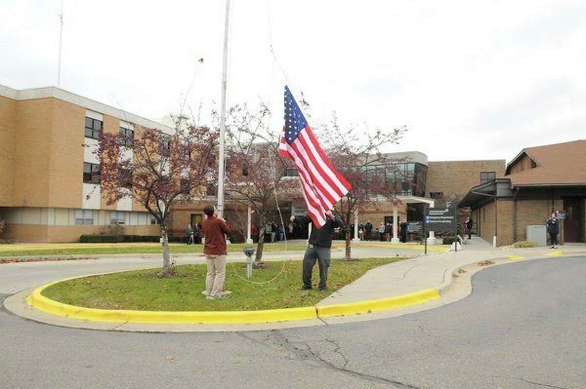 In this 2018 photo, Spectrum Health employees raise their flags in honor of those who have fought for their country. (Courtesy photo)