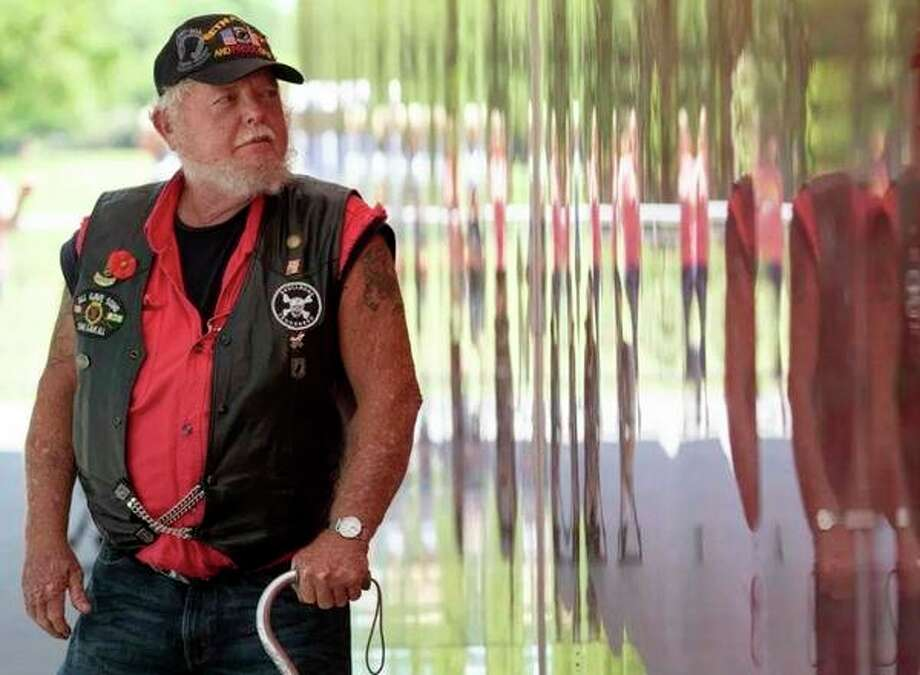 Vietnam veteran Marvin Nolin of Dover, Tenn., visits the Poppy Wall of Honor on the National Mall in Washington, on May 24. The poppy flower has come to symbolize sacrifices, and more than 645,000 poppies fill a wall stretching 133 feet by 8½ feet tall. Each of those flowers represents an American servicemember who has fallen in the defense of freedom going back to World War I. (Carolyn Kaster/AP Photo) / The Palm Beach Post, Fla.