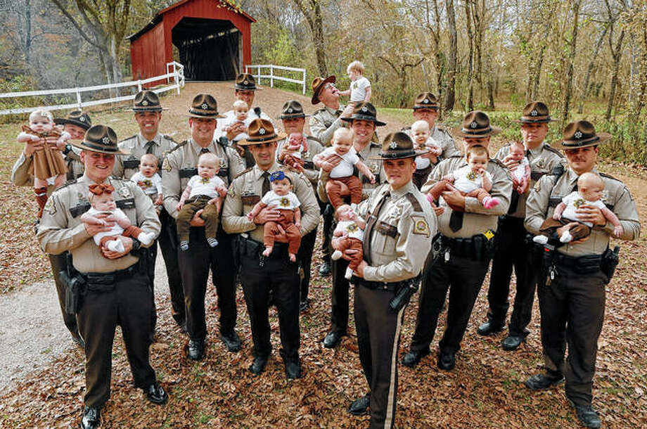 Some 14 Jefferson County (Missouri) Sheriff's deputies pose Monday for a photo with their babies at Sandy Creek Covered Bridge in Jefferson County. They are from left, with their babies: Adam Lambrich with Lilliana; A.J. Kausler with Lucy; Matt Moore with Luca; Scott Ehrhard with Hudson; Andy Sides with Carter; Greg Bohn with Evelyn; Dustin Isenhart with Kash; Nick Gamm with Gweneth; Colby McCreary with Sawyer; Cody Cawvey with Micah; Shawn Loness with Connor; Andrew Griffon with Kinsley; Kevin Karl with Kade; and Roger Waeckerle with Wyatt. Photo: J.B. Forbes | St. Louis Post-Dispatch Via AP