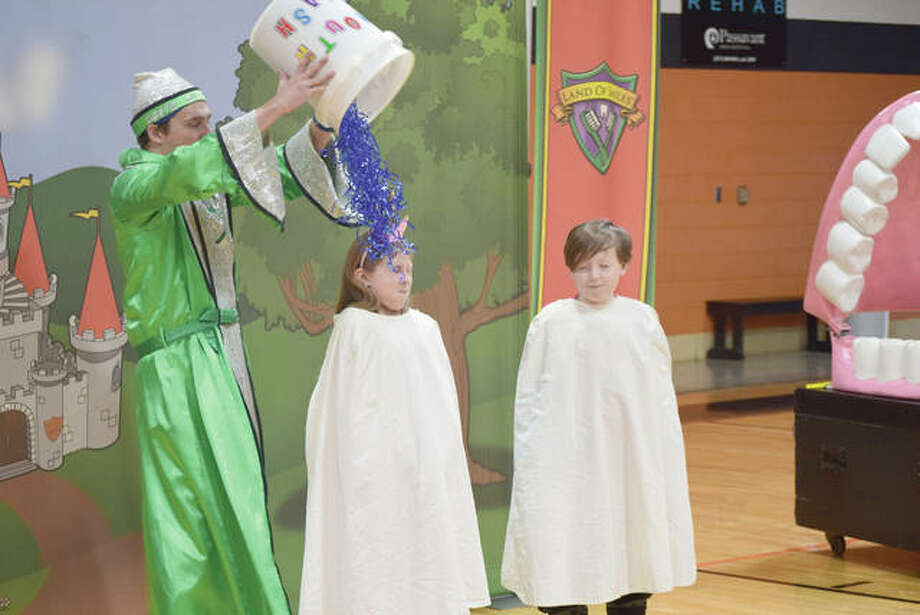 The Tooth Wizard pours a bucket of streamers — meant to represent mouth wash — over Meredosia-Chambersburg Elementary School students Maci Schmitz, 8, and Max Battefeld, 9, who volunteered Tuesday to be teeth. The Tooth Wizard and his foe, PlaqueMan, are part of Delta Dental of Illinois Foundation's Land of Smiles program to teach kids dental health. For more photos, go to myjournalcourier.com. Photo: Marco Cartolano | Journal-Courier