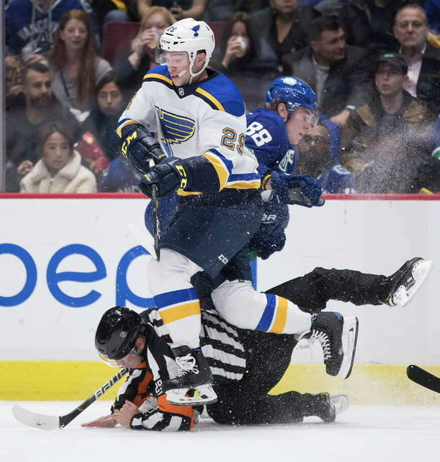 The Blues' Vince Dunn and the Canucks' Adam Gaudette (88) and referee Ian Walsh collide during the second period Tuesday night in Vancouver, British Columbia. Photo: Associated Press