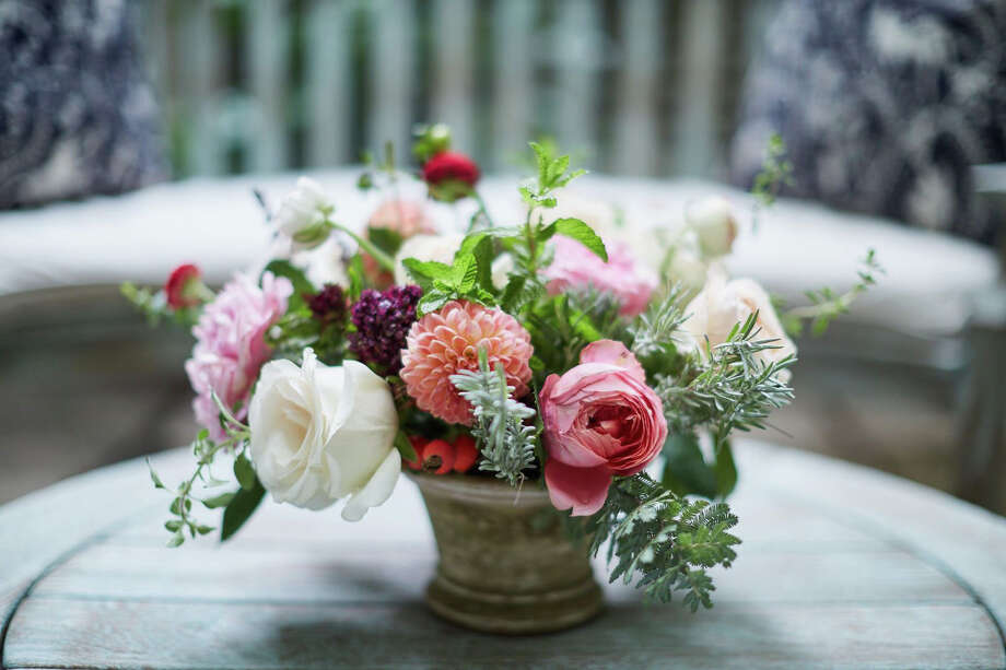 A Cathy Graham arrangement includes dahlias, garden roses and ranunculus plus fragrant rosemary,which signifies remembrance. It would make a nice Mother's Day or get-well arrangement. Photo: Quentin Bacon / The Washington Post